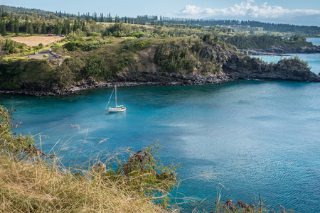 A yacht is anchored in a cove on the Northwest Maui shoreline. Reklamní fotografie