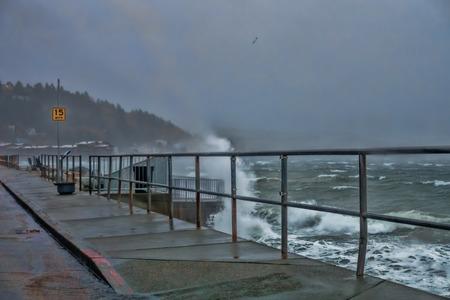 Stormachtige golven breken tegen de muur van de kustlijn van West Seattle.
