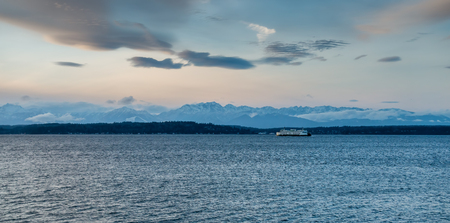 A ferry moves across the Puget Sound with the Mountains in the distance. Фото со стока