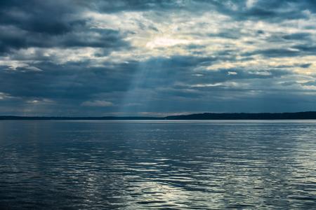 Subtle rays of light break through the clouds over the Puget Sound. Banco de Imagens