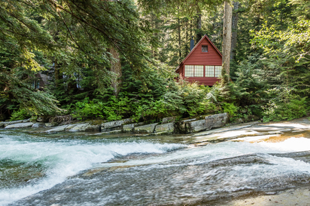 Clear water rushes along  on Denny Creek in Washington State. An A-frame cabin is in the background.