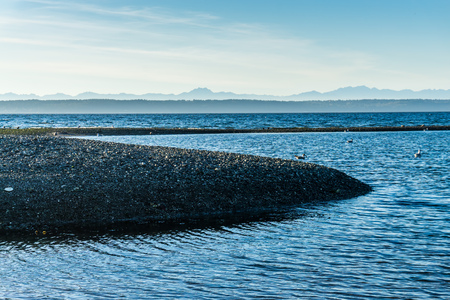 A view of a tide pool with mountains in the distance in the Pacific Northwest. Stock Photo