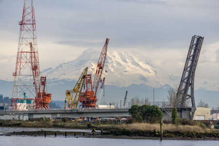 a view of a bridge, crane and Mount Rainier at the Port of Tacoma.