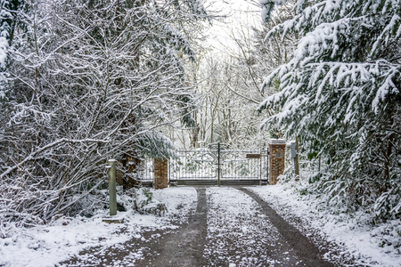 A view of a private gate that is surrounded by snow.