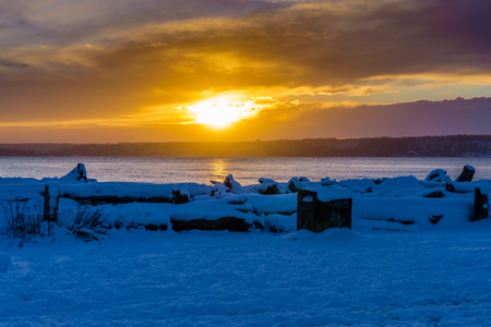 Snow covers the ground as the sun set over the Puget Sound. Stock Photo