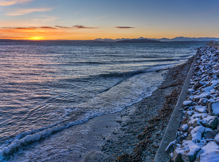A view of the setting sun and the West Seattle shoreline in winter.