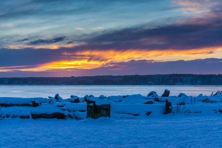 Snow covers the ground as the sun sets at Normandy Park, Washington.