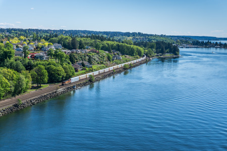 A railroad train moves along the shore of the Tacoma Narrows waterway. Stockfoto