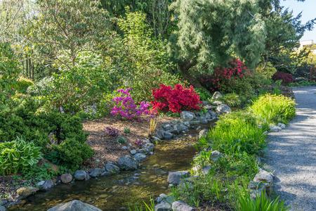 A stream with rock flows through a garden.