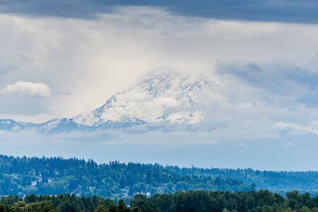 Mount Rainier is surrounded by clouds with trees below.