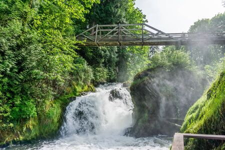 A waterfall bulges out with water in Tumwater, Washington. A bridge is above. 版權商用圖片