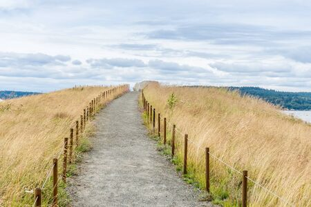 A dirt path leads up a small hill at Dune Peninsula Park in Tacoma, Washington. Stock Photo