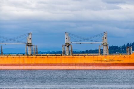 A view of a section of an orange tanker ship.