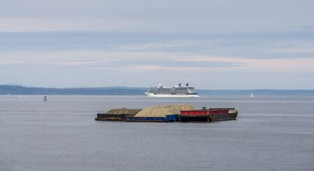 A barge and cruise ship in the Port of Seattle. Stock Photo