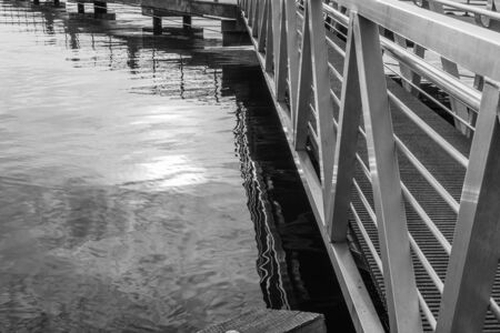 Reflections in the water of a pier at Gene Couldon Park in Renton, Washington. Фото со стока - 132558557