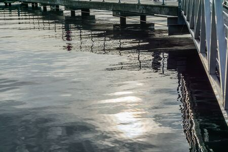 Reflections in the water of a pier at Gene Couldon Park in Renton, Washington. Фото со стока - 132591998