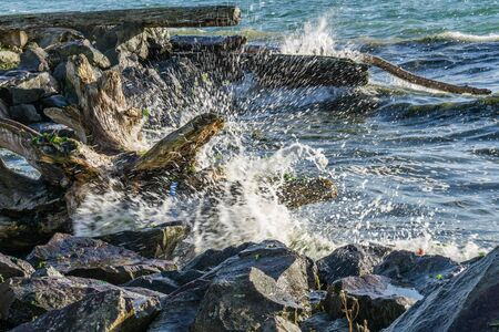 Whitewater flys up as wave hit shore on the Puget Sound. Stock Photo