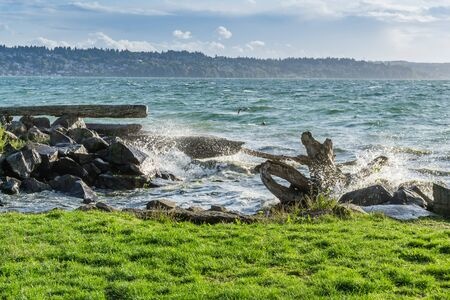 Waves from the Puget Sound hit rocks on the shoreline in Des Moines, Washington.