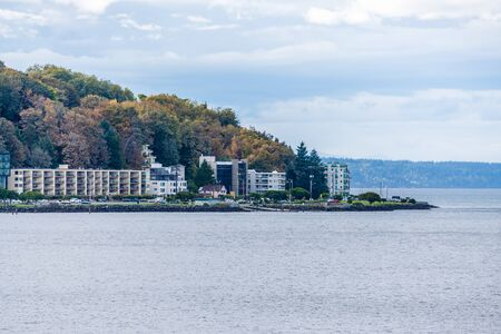 Autumn trees and buildings on the West Seattle shoreline.