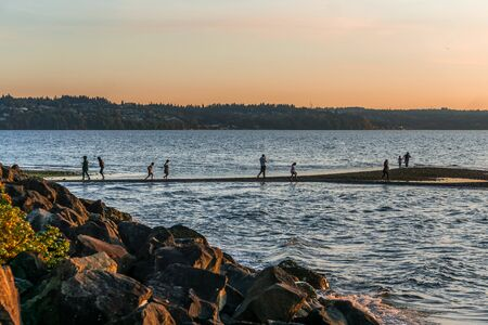 Poeple enjoy the seashore as the sun sets in the Pacific Northwest.