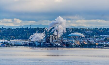 Steam rises from a factory with the Tacoma Dome nearby. 写真素材