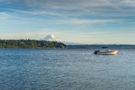 Snow covers stunning Mount Rainier in Washington State with a boat in the foreground.