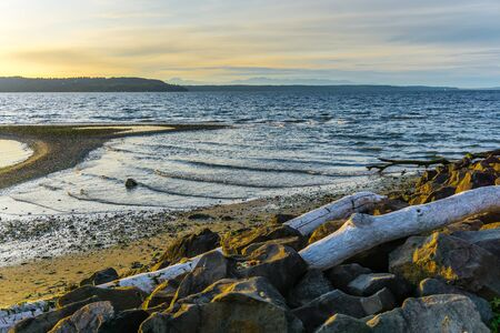 Waves roll onto the shore at Saltwater State Park in Des Moines, Washington. The sun is setting. 写真素材