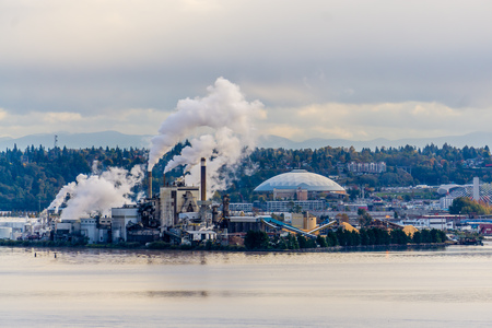 Steam rises from a factory with the Tacoma Dome nearby. 報道画像