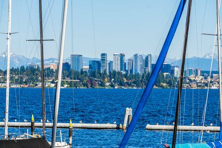 Boat are moored in a Lake Washington marina with the Bellevue skyline in the distance.
