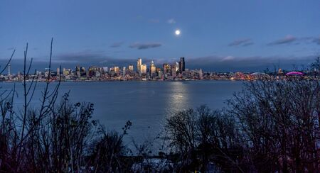 A bright full moon shines over the Seattle skyline.