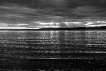 Rays of light sine down through dark clouds over the Puget Sound.