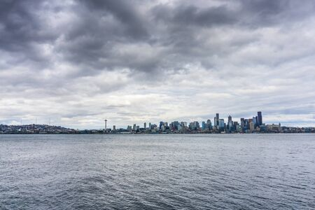 Dark storm clouds hover over the Seattle skyline.