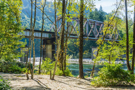 A train trestle spans the Skykomish River in Washington State. Trees in the foreground.