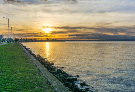 The sun is sinking toward the horizon at Alki Beach in West Seattle, Washington.