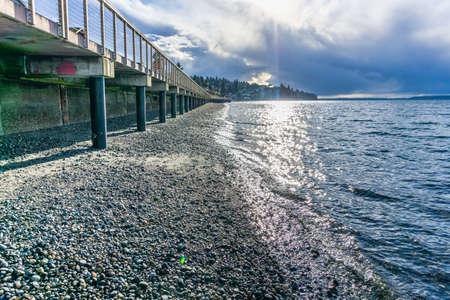 Rsys of light shine down on the Puget Sound at Redondo Beach, Washington.