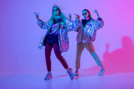 Young stylish girls dancing in the Studio on a colored neon background. Music dj poster design.
