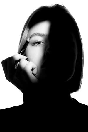 Portrait of a girl on a white background. Fashion model uses cosmetic pencil for eyebrows and eyelids. Black-white.