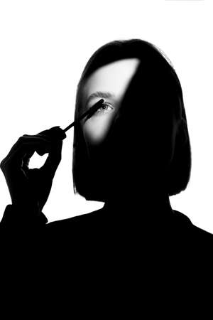 Epic promotional portrait of a girl with applicator and mascara brush. Black and white minimalistic advertising concept. Stok Fotoğraf