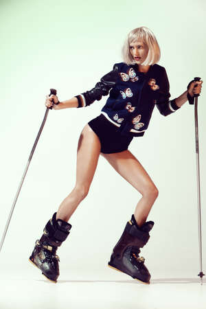 all fashionable blonde model in ski boots and ski poles. Winter sports. Haute couture. Banque d'images