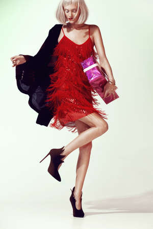 Perfect girl model in a designer red dress and chic high-heeled shoes. With a gift box. Birthday or new year party.