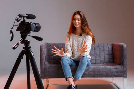 Young teen girl vlogger makes a video stream on the couch at home. A video camera on a tripod.