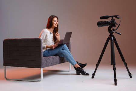 Young teen girl blogger makes a video stream on the couch at home. A video camera on a tripod and a laptop.