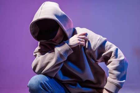 Retrato épico moderno de bboy con una sudadera con capucha de luz de neón. Debajo del capó. Cara oscura. Misterioso y genial.