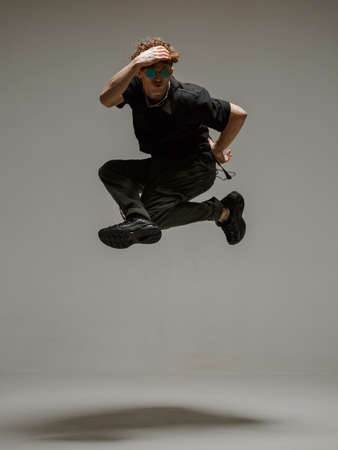 Guy dancing contemporary dance in studio. Neutral grey background. Acrobatic bboy dancer.