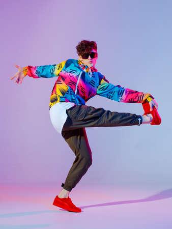 Boy dancing in neon light studio. Acrobatic dancer. Banco de Imagens