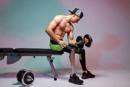 A young muscular man with a disability with a prosthetic leg is training in a gym with dumbbells. Motivation poster Reklamní fotografie