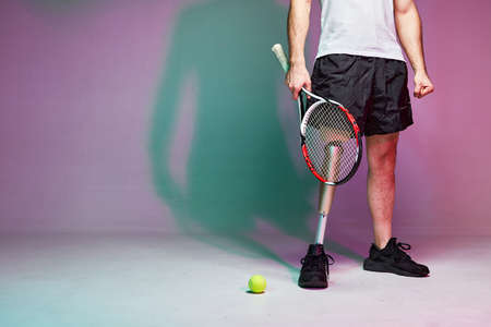 A young man with a disability with a prosthetic leg play in tennis. Motivation poster.