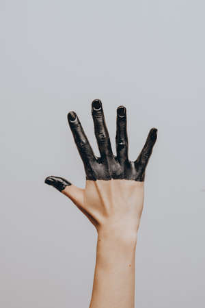 Elegant female hand dipped in black paint on a light background. Isolated. Gesture Foto de archivo