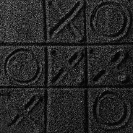 Playing on the black sand beach. Drawing with finger. Cross-zero. Tic-tac-toe game.
