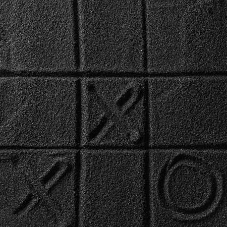 Playing on the black sand beach. Drawing with finger. Cross-zero. Tic-tac-toe game. Stok Fotoğraf